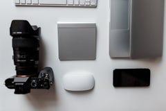 Bästa sikt av den yrkesmässiga fotografen för tabell som har en modern kamera, tangentbordet, den trådlösa musen, mobiltelefonen, arkivfoto