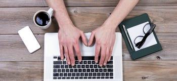 Bästa sikt av det funktionsdugliga skrivbordet med händer på bärbar datortangentbordet med nolla Fotografering för Bildbyråer