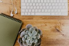 Bästa sikt av det moderiktiga träkontorsskrivbordet med tangentbordet, vita hörlurar och kontorstillförsel fotografering för bildbyråer
