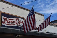 Bästa sikt av det Pepsi tappningtecknet och USA flaggor på Kissimmee den gamla staden royaltyfri bild