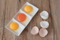 Bästa sikt av det rå ägget med gul äggula och brutna Shell Halves Fotografering för Bildbyråer