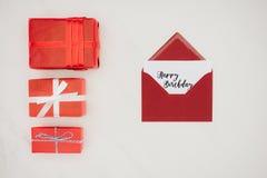 bästa sikt av det röda kuvertet med bokstäver för LYCKLIG FÖDELSEDAG på papper och rad av gåvaaskar Royaltyfri Bild