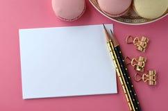 Bästa sikt av det tomma anmärkningskortet, bärbara datorn, mobiltelefonen och franskamacarons på rosa bakgrund Kvinnligt workspac royaltyfri foto
