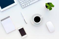 Bästa sikt av det vita kontorsskrivbordet med den moderna elektronikbrevpapper och blomman Royaltyfri Foto