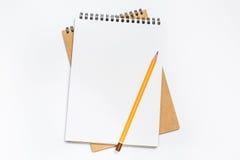 Bästa sikt av det vita skrivbordet med den tomma anteckningsboken i mitt Royaltyfri Foto