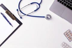 Bästa sikt av doktorsskrivbordet med stetoskopet, latptop, piller och tomt papper på skrivplattan med kopieringsutrymme royaltyfri bild