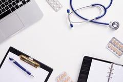 Bästa sikt av doktorsskrivbordet med stetoskopet, latptop, piller och tomt papper på skrivplattan med kopieringsutrymme royaltyfria foton