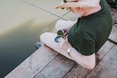 Bästa sikt av en åldrig man som rymmer beten för att fiska arkivbild
