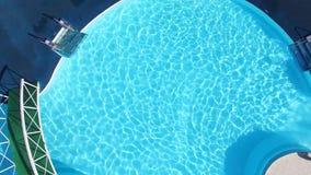 Bästa sikt av en andelsfastighetsimbassäng med två tomma vita deckchairs plats Bästa sikt av den lyxiga simbassängen ytter stock video