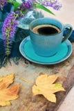 Bästa sikt av en blå kopp kaffe, purpurfärgade blommor i en vas och guld- sidor på träbakgrund royaltyfri fotografi