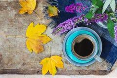 Bästa sikt av en blå kopp kaffe, en blå rutig halsduk, purpurfärgade blommor i en vas och guld- sidor på träbakgrund royaltyfri foto