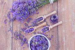 Bästa sikt av en bunke och träskedar med nya lavendelblommor, nödvändig olja för lavendel och en bukett av lavendel Royaltyfri Foto