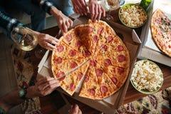 Bästa sikt av en grupp av vänner som äter stor pizza arkivfoton