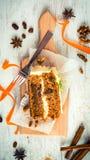 Bästa sikt av en hemlagad morotkaka med russin, valnötter och kanel över vit träbakgrund Gräddostglasyr på kaka Royaltyfri Bild