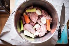 Bästa sikt av en kokkärl med kött, tungan, grönsaker och kryddor Arkivfoton