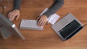 Bästa sikt av en man som arbetar på hans bärbar dator i härlig kontorsinre stock video