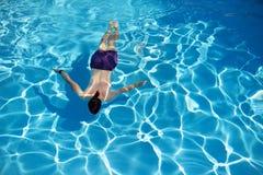 Bästa sikt av en mansimning i en simbassäng på solig sommardag Arkivbilder