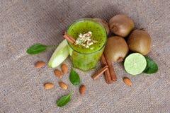 Bästa sikt av en näringsrik dryck från kiwi, äpplet och limefrukt på en ljus tygbakgrund Healthful ingredienser arkivfoto