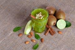 Bästa sikt av en näringsrik dryck från kiwi, äpplet och limefrukt på en ljus tygbakgrund Healthful ingredienser royaltyfri foto