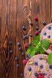 Bästa sikt av en rosa smoothie En närbild av en söt yoghurt på en träbakgrund Smoothie med hallon, blåbär och mintkaramellen royaltyfri bild