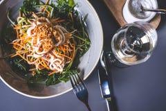 Bästa sikt av en sallad av asiatisk kokkonst och ett exponeringsglas av vin Arkivbilder