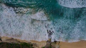 Bästa sikt av en sandig strand med turkoshav- och avbrottsvågor royaltyfri foto