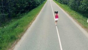 Bästa sikt av en slank kvinna som joggar i den öppna luften _ arkivfilmer