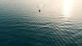 Bästa sikt av en snabb motorbåt som svävar till och med det öppna vattnet Hav på solnedgången arkivfilmer