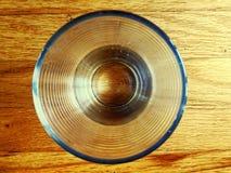 Bästa sikt av ett dricka exponeringsglas på en skogsbevuxen tabell Arkivfoto