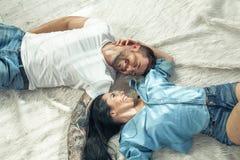 Bästa sikt av ett härligt par som lägger över vit bakgrund m?rkt flickah?r long de ?r f?r?lskade arkivfoto