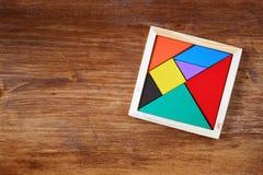 Bästa sikt av ett saknat stycke i ett fyrkantigt tangrampussel, över trätabellen Royaltyfri Foto