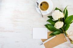 Bästa sikt av ett tomt hälsningkort, det kraft kuvertet, pionbuketten och en kopp kaffe över vit trälantlig bakgrund Arkivbild