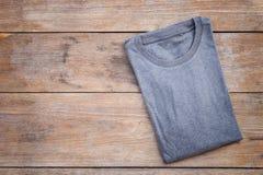 Bästa sikt av färgT-tröja på grå wood planka Arkivbild