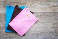Bästa sikt av färgT-tröja på grå wood planka arkivbilder
