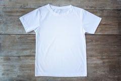 Bästa sikt av färgT-tröja på grå wood planka Arkivfoton