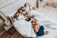 Bästa sikt av familjen som tillsammans sover i säng arkivfoton