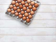 Bästa sikt av fega ägg i en kartong på en vit trätabell med kopieringsutrymme Arkivfoto