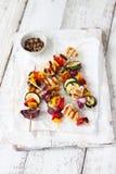 Bästa sikt av fega steknålar eller shashlik med grillade grönsaker royaltyfria foton