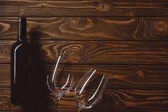 bästa sikt av flaskan av rött vin med tomma exponeringsglas arkivfoto