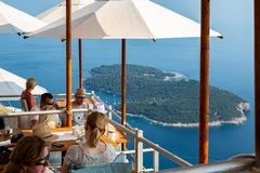 Bästa sikt av folk på en restaurang på en bergöverkant med en ö i Adriatiskt havet royaltyfri bild