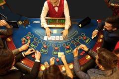 Bästa sikt av folk som spelar poker på tabellen i en kasino royaltyfri fotografi