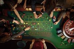 Bästa sikt av folk som spelar rouletten på tabellen i en kasino arkivfoton