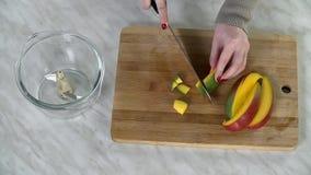 Bästa sikt av framställning av små stycken av mango på matlagningskrivbordet arkivfilmer