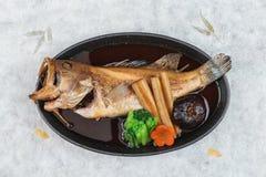 Bästa sikt av Fried snapper med rädisan, moroten, shiitaken och choy summa i varm platta på japanskt papper för washi Royaltyfria Foton