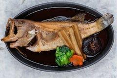 Bästa sikt av Fried snapper med rädisan, moroten, shiitaken och choy summa i varm platta på träplattan på japanskt papper för was Arkivbilder