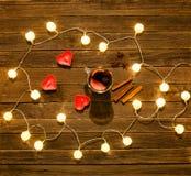 Bästa sikt av funderat vin med kryddor, stearinljus i formen av en hjärta, kanelbruna pinnar, stjärnaanis på en trätabell Girland Arkivfoto