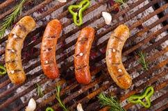 Bästa sikt av fyra grilla korvar på grillfestgaller med någon art BBQ i trädgården Bayerska korvar arkivfoto
