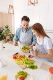Bästa sikt av gladlynt fader- och dottermatlagningsallad arkivfoton