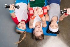 Bästa sikt av gulliga barn i sportswearen som ligger på matt yoga och övar med hantlar i idrottshall royaltyfri fotografi