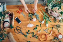 Bästa sikt av händer av blomsterhandlaren för ung kvinna som skapar buketten av blommor Arkivbilder
